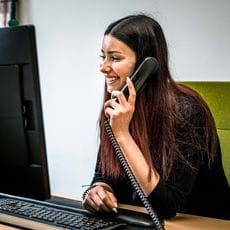 ein Lehrling telefoniert und blickt auf den Computerbildschirm