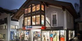 Bründl Sports well-lit shopwindow in Saalbach Zentrum - evening view <br/>