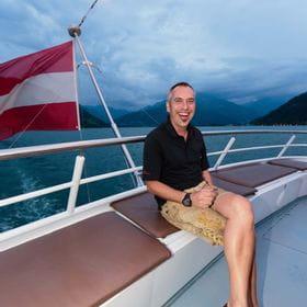Manfred Mucknauer sitzt am Deck eines Schiffes vor der Railing