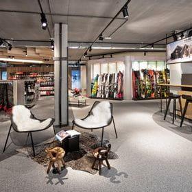 gemütliche Sitzecke im Vordergrund, Skibekleidung und Skiwand im Hintergrund <br/>