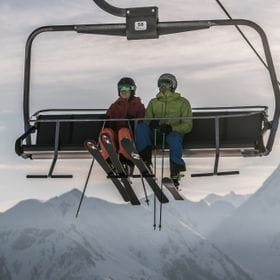 two skier are sitting in a chair lift