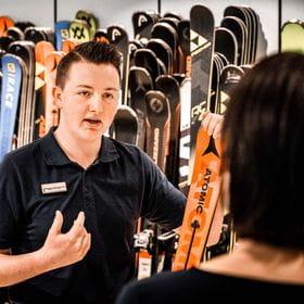 ein Mitarbeiter präsentiert einen Ski