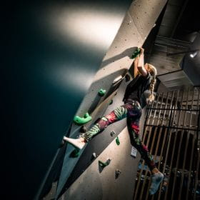 Young girl who is climbing at the Bründl Sports wall for bouldering in their shop in Saalfelden