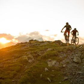 zwei Mountainbiker sind in den Bergen unterwegs während im Hintergrund die Sonne untergeht