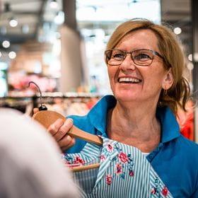 an employee hands over a shirt to a customer