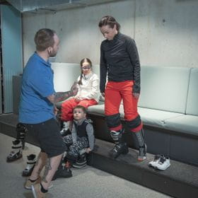a woman tries a skiing shoe, while a employee gives her advice