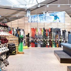 Skischuhe und Sitzbänke im Vordergrund, Skiwand im Hintergrund