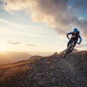 a mountainbiker drives through mountainous terrain