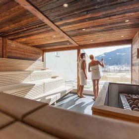 Ein Paar genießt die Aussicht in der Sauna im Tauern Spa Kaprun