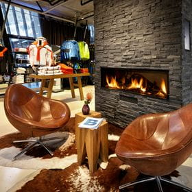 Cozy seating area by the fire, skiclothing in the back <br/>