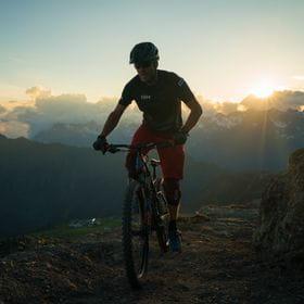 ein Mountainbiker fährt durch die Berge während die Sonne schon fast untergegangen ist