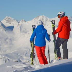 two skiers are talking to each other in front of the mountains
