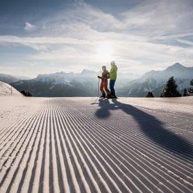 zwei Skifahrer stehen auf einer frisch präparierten Piste