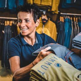 eine Mitarbeiterin ordnet T-Shirts