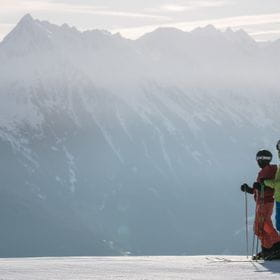 the skiers in front of a massive mountain crest are shown