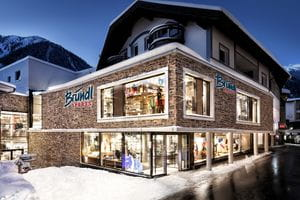 Bründl Sports Ischgl Zentrum well-lit shopwindow - winter evening view <br/>
