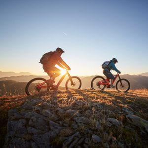 two mountainbikers are riding on a mountain ridge, while the sun sets in the background