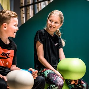 Young boy and girl who are sitting on playing toys in the kids corner at Bründl Sports in Saalfelden