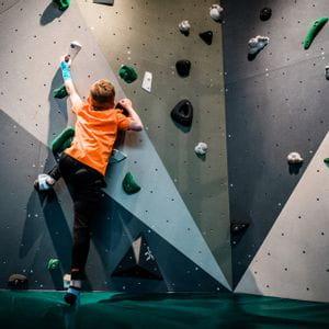 Junge mit orangem T-Shirt beim Bouldern bei Bründl Sports in Saalfelden
