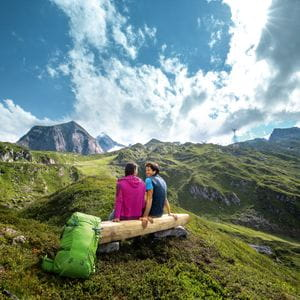 two hikers are sitting on a bench at Kitzsteinhorn