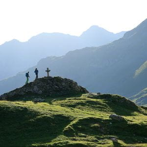 three hikers are climing a hill in a mountain landscape