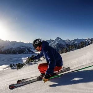 ein Skifahrer auf der Piste mit starker Schräglage
