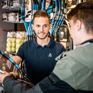 A customer gives his tennis racket to a staff member