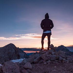 ein Läufer betrachtet den Sonnenuntergang in den Bergen