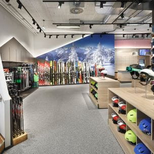 Skihelmets and skisticks in the front, colourful skiwall behind <br/>