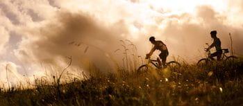 zwei Fahrradfahrer auf einem Pfad, Wolken im Hintegrund