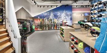 Skihelme und Skistöcke im Vordergrund, bunte Skiwand im Hintergrund <br/>