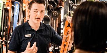 Verkäufer bei Bründl Sports erklärt einer Kundin einen Atomic Ski