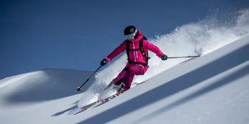 Eine Dame in einem pinken Ski-Outfit von Rossignol zieht ihre Schwünge durch den Tiefschnee