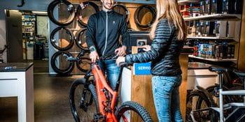 Eine Kundin gibt ihr Fahrrad zum Bikeservice ab