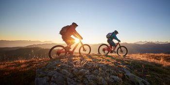 zwei Mountainbiker fahren auf einem Berggrat, im Hintergrund der Sonnenuntergang