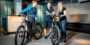 A couple is renting bicycles which are handed over to them by an assistant