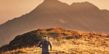eine Person läuft in der Berglandschaft, im Hintergrund die entfernten Berge gefärbt in unterschiedlichen Orange-tönen