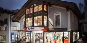 Beleuchtetes Schaufenster des Bründl Sports Saalbach Zentrum Shops - Abendaufnahme <br/>