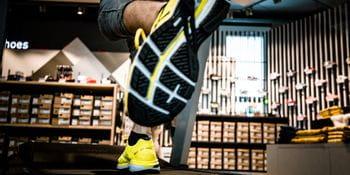 Eine Detailaufnahme des Profil eines Laufschuhs während jemand auf einem Laufband läuft