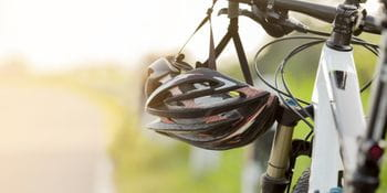 a helmet is hanging from the handlebar of a bycicle