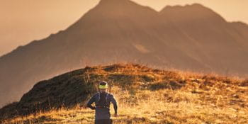 a persons runs through the mountain landscape, in the background the distant mountans coloured in different tones of orange.