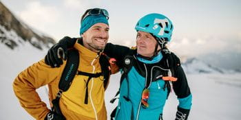 Two skitourers, arm in arm, dressed in products from Ortovox, Mammut and Martini