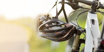 a helmet hanging from a handlebar of a bycicle