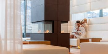 couple sits in the relaxing area in front of a fireplace
