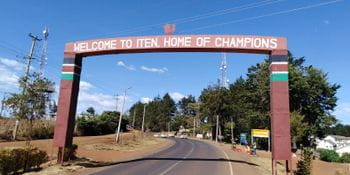 "an archway over the road with the slogan ""Welcome to Iten. Home of Champions"""