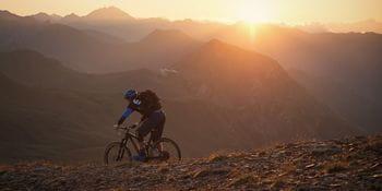 ein Mountainbiker fährt durch die Berglandschaft, während im Hintegrund die Sonne untergeht