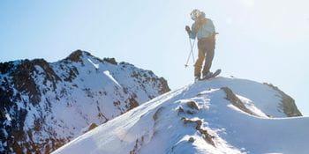 Ein Freerider steht auf einem Berg und blickt hinab ins Tal auf seine Abfahrt