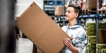 ein Logistik-Lehrling kommissioniert ein Paket