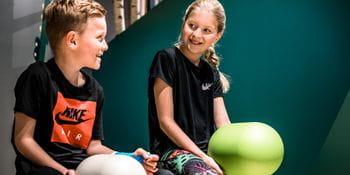 Junge und Mädchen auf zwei Spielfiguren in der Kinderspielecke bei Bründl Sports in Saalfelden