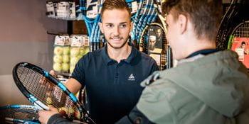 Ein Kunde überreicht einen Tennisschläger an einen Mitarbeiter von Bründl Sports